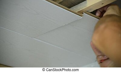 Worker makes the ceiling of MDF panels - Worker makes the...