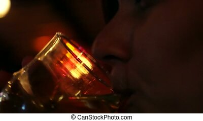 Young beautiful woman sipping red sweet drink in bar and...
