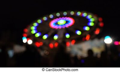 Theme park at night. Blurred spinning LED lit attraction. 4K...