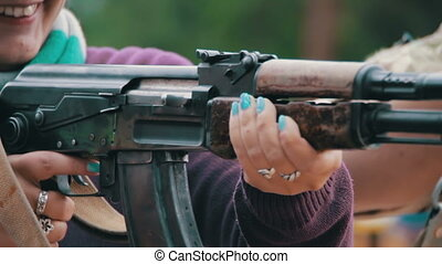 Woman Holds in Hands Machine Gun and aiming a weapon in...