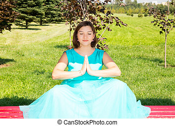 Beautiful pregnant woman meditating on with big belly