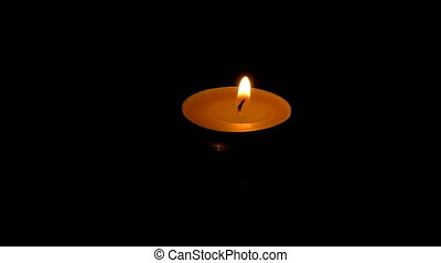 A single candle floating on water