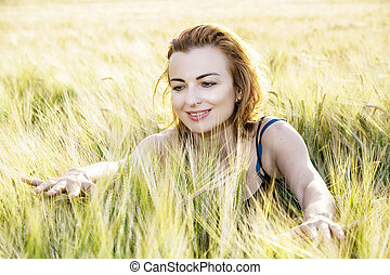 Lovely woman in the wheat cobs by sunset, natural beauty -...