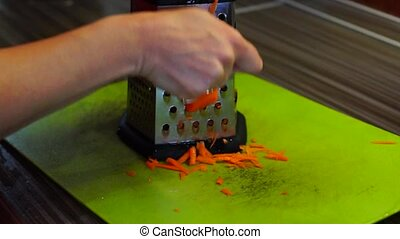Grating the carrots on grater - Hand is grating the carrots...