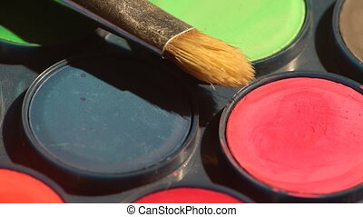 Turning colors set and a brush - A set of watercolor paints...