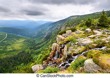 Beautiful waterfall above a deep green valley with mountains