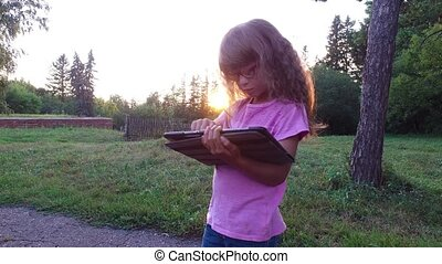 Girl child in glasses enthusiastically working on a tablet...