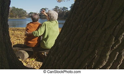 senior couple at lake in autumn