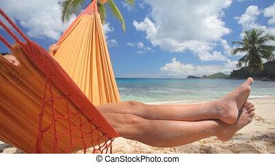 legs of woman in hammock - womans leg in hammock on sandy...