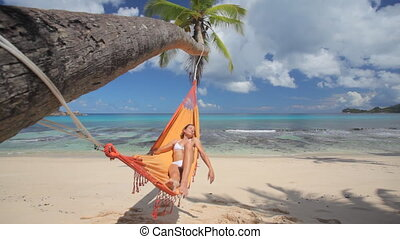 woman in hammock on palmtree - woman in white bikini...