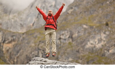 happy man in red - male hiker very happy about reaching top...
