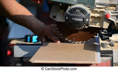 Man sawing MDF board with circular saw - Man sawing MDF...