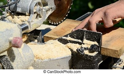 Man sawing wooden plank with circular saw - Man sawing...