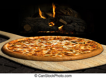 Wood Fired Pizza - Pizza resting on a pizza peel near an...