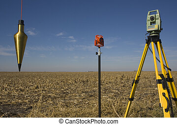 Total station, prism and plumb-bob in the field