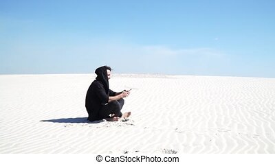 Communication by phone in desert - A guy sitting in the...
