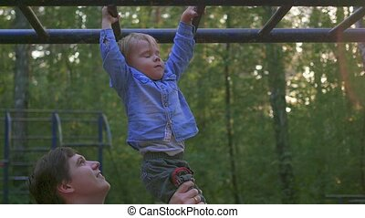 the father helps the child to climb on the horizontal ladder...