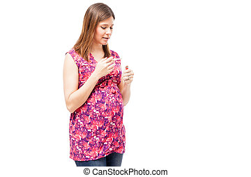 Pregnant woman lighting a cigarette - Portrait of an...
