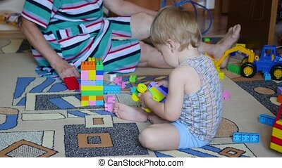 the small child with the grandmother playing with toys at...