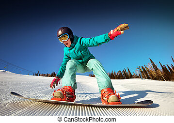 Snowboarder posing on blue sky backdrop in mountains trick -...
