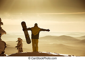 Snowboarder posing on blue sky backdrop in mountains fog