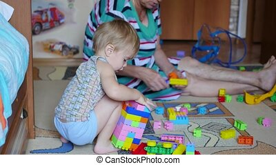 the small child with the grandmother playing with toys at home