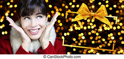 woman with christmas box frame in golden lights background