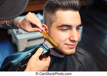 Young man having beard shaven - Young smiling man having his...