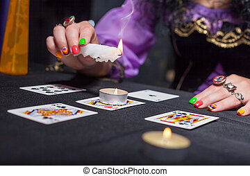 Sorceress telling fortunes using cards and candles