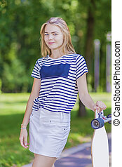 Youth LIfestyle Concepts. Blond Caucasian Teenage Girl Posing With Long Skateboard in Green Forest.