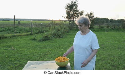 Woman carrying a bowl of mushrooms chanterelles