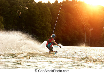 WakeBoard Surfing Water Sport - Wakeboarder surfing across a...