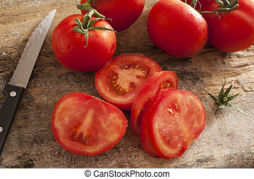 Sliced succulent red tomatoes beside serrated knife and...