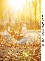 Mother and daughter throw up dead leaves. - Family walk....