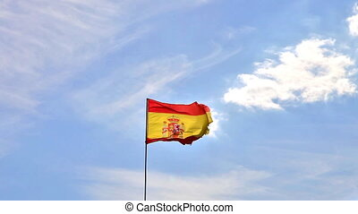 Flag of Spain waving in a cloudy sky with seagulls flying....