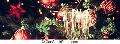 Two glasses of champagne with Christmas tree background....