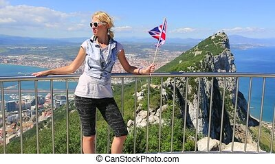 The symbols of Gibraltar - Tourist woman holding an English...