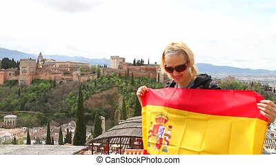 Alhambra Royal Palace - Tourist woman holding an Spain flag...