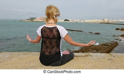 the Yoga lotus pose - Blonde girl in lotus pose in front of...