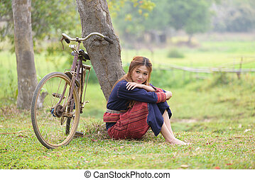 Young asian women sitting next to tree with bike in rice...