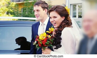 Happy married couple stand by the car in wedding day and...