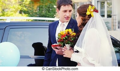 Happy married couple stand by the car in wedding day in...