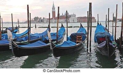 Gondolas moored by Saint Mark square in sunrise. San Giorgio...