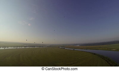 Top view of air balloons fly over field and river