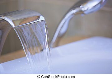 Tap with flowing water - Close-up view of the tap with...