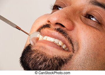 Dental treatment - An Asian Indian man getting dental...