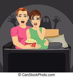young couple watching horror movie at home sitting with popcorn on sofa