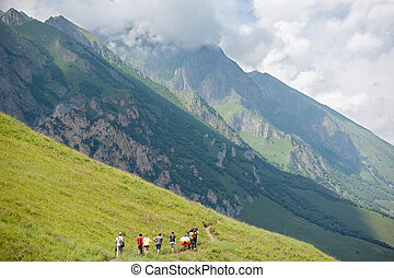 people walking along track in the mountains