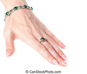 Feminine hand, bracelet, ring with green stone on white...