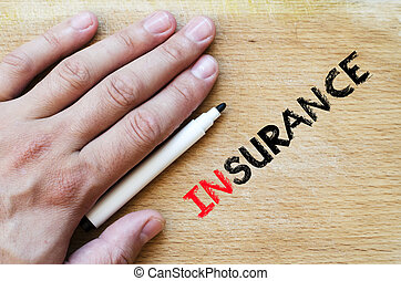 Insurance text concept - Human hand over wooden background...